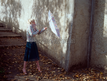 woman holding inside out umbrella