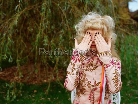 woman in garden covering eyes