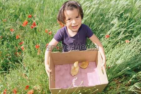 girl carrying a cardboard box with