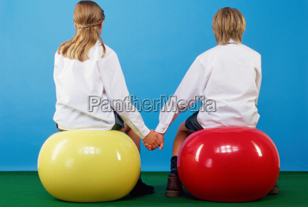girl and boy sitting on exercise