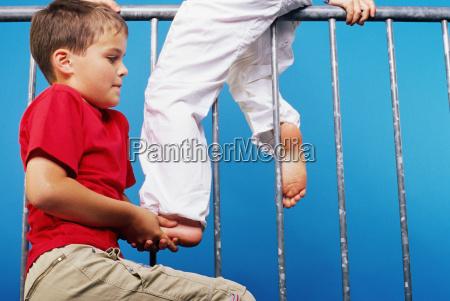 boy helping friend onto a railing