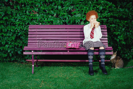 girl on a bench eating a