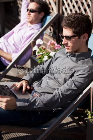 two men sunbathing on deck chairs