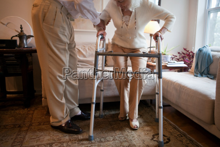 senior man assisting wife with walking