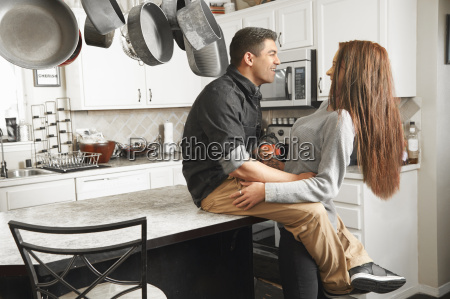 young couple hugging at kitchen counter