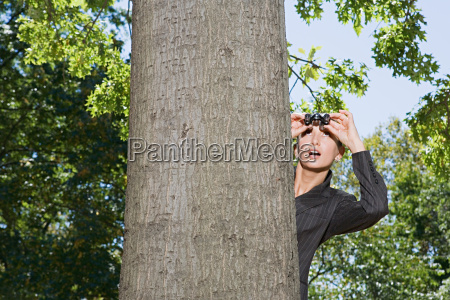 businesswoman spying from behind a tree