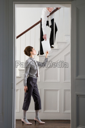 woman passing paper to man