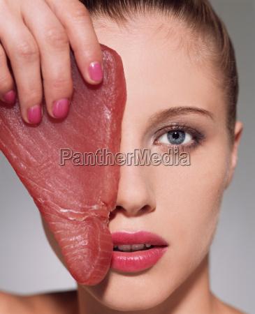 woman holding tuna steak over her