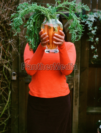 woman holding a vase of carrots