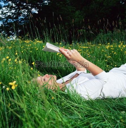 woman reading book on grass