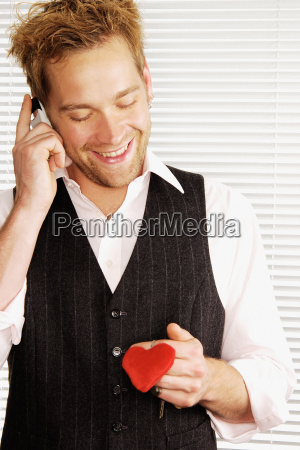 smiling man holding heart shaped keyring