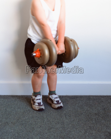young boy lifting a dumbbell