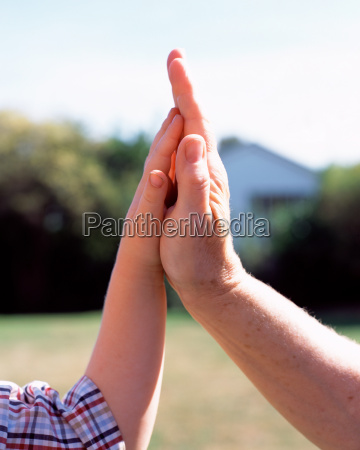 hand of man and boy touching