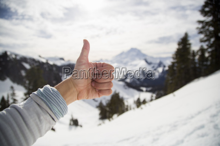 female hand making thumbs up in