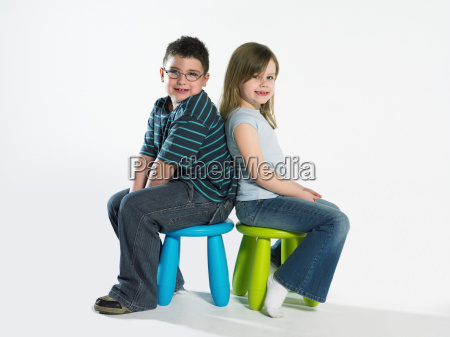 girl and boy sitting on stools
