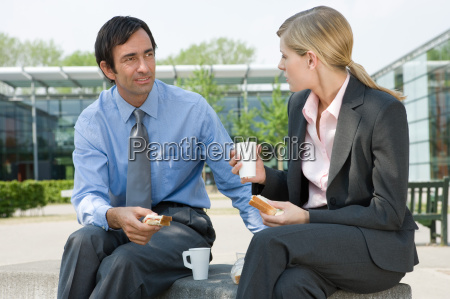businesswoman and businessman eating sandwiches outdoors