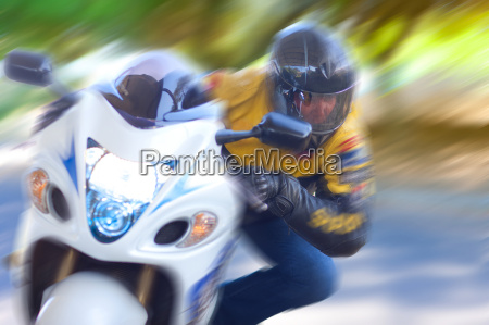 blurred view of man riding motorcycle