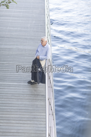 senior businessman leaning against hotel terrace