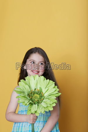 girl holding a large green flower