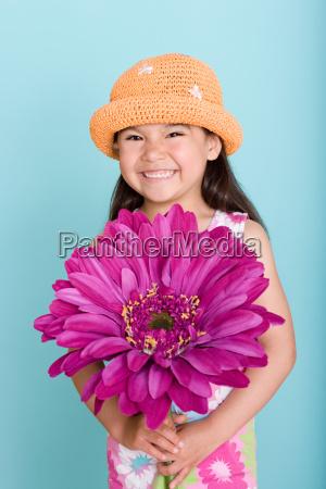 asian girl holding a large flower