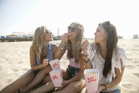 three young women sitting on beach