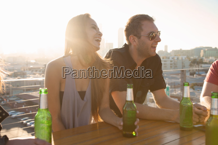 two adult friends drinking beer at