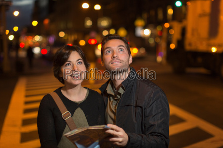 couple reading city map at night