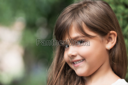 smiling attractive little girl peeks at