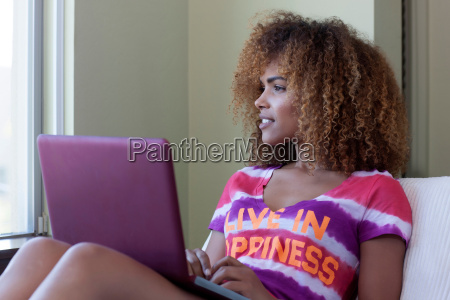 mid adult woman sitting using laptop