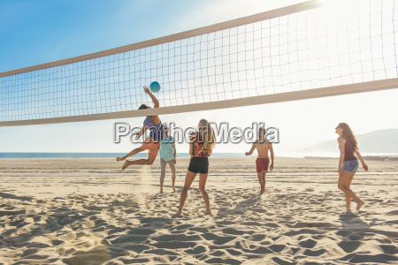 group of friends playing volleyball on