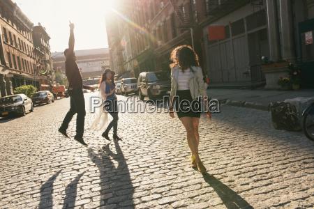 three mid adult friends jumping