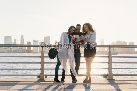 three mid adult friends taking smartphone