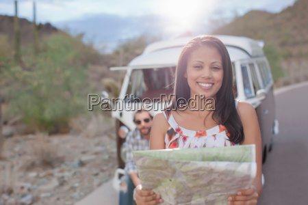 young woman holding map on road