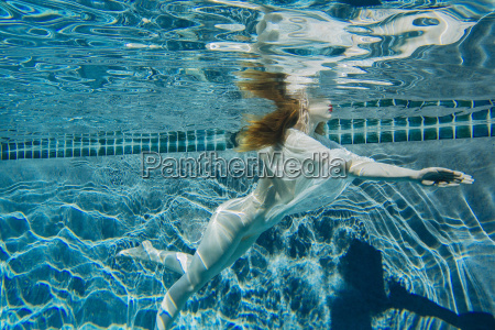 young woman swimming underwater wearing thin