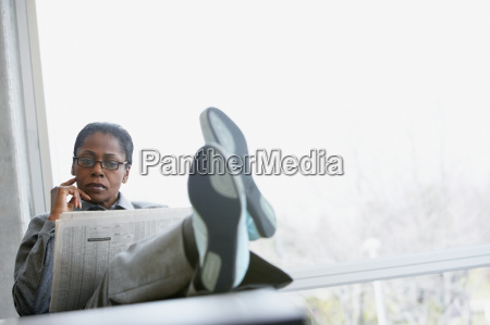 businesswoman reading a broadsheet newspaper