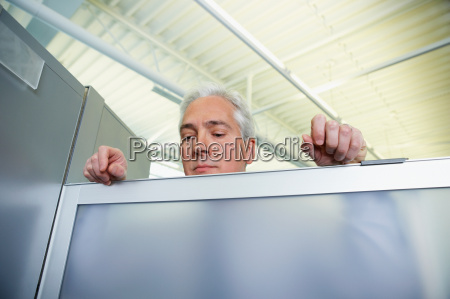 man peering over a glass partition
