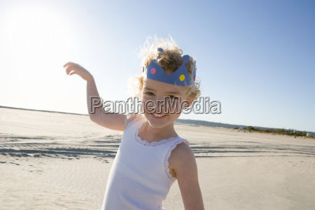 girl wearing crown on beach