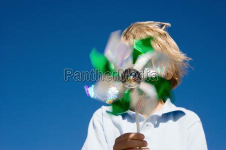 boy holding pinwheel in front of