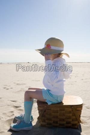 girl sitting on picnic basket on