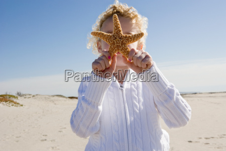 girl holding starfish in front of