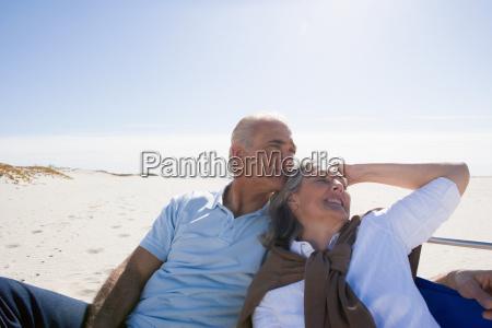 senior couple relaxing on beach