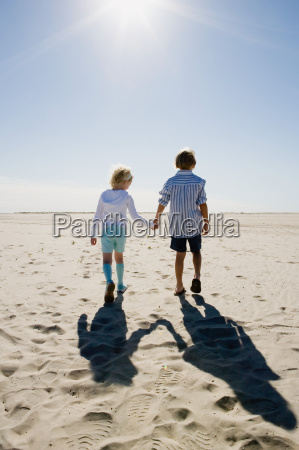 boy and girl holding hands walking