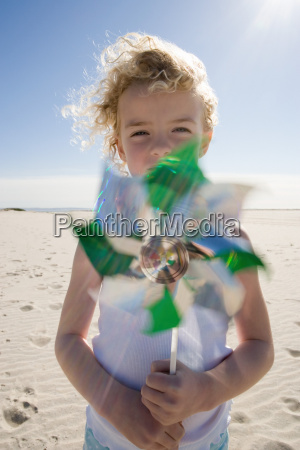 girl holding pinwheel on beach