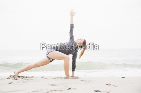 mid adult woman meditating on beach