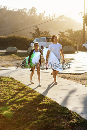 couple carrying surfboards walking towards beach