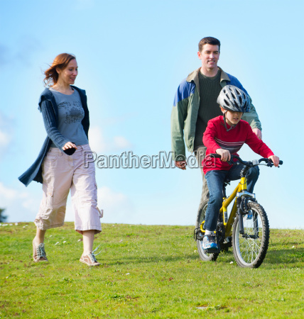 parents watching son riding bicycle