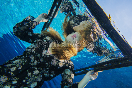 young woman underwater holding frame