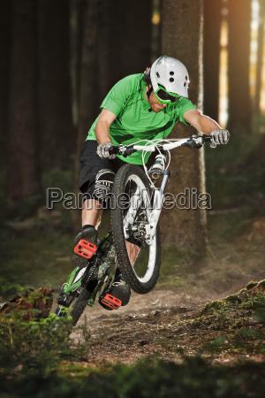mountain biker riding on back wheel