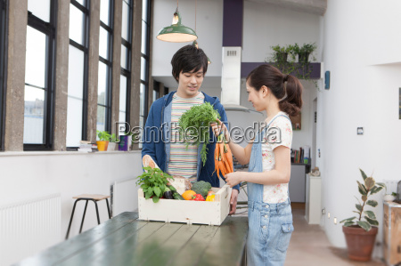 young couple in kitchen with box