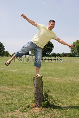 man balancing on tree stump